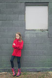 Girl in red on grey wall Royalty Free Stock Photo