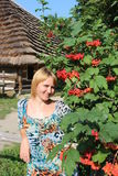 Girl with red guelder-rose besides an rural house Royalty Free Stock Photo