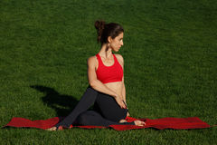Girl on a red gymnastic mat. Woman practices yoga in nature Royalty Free Stock Images