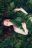 Girl with red hair in an armful of ferns. Women with red hair in an armful of ferns Royalty Free Stock Photo