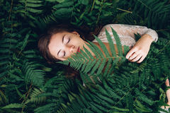 Girl with red hair in an armful of ferns. Women with red hair in an armful of ferns Royalty Free Stock Photography