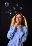 Girl with red hair blow bubbles. Beautiful girl with red hair blow bubbles Royalty Free Stock Image