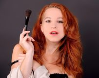 Girl with red hair and brush. Girl with red hair and make-up brush royalty free stock images