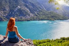 Girl with red hair on cliff top of canyon with green water