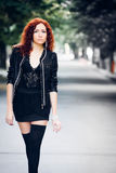 Girl with red hair. Cute girl with red hair on city road whith green trees alley stock photography