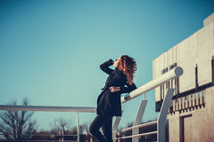 Girl with red hair. Cute girl with red hair standing on the building background against the blue sky stock photo