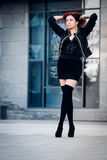 Girl with red hair. Fashion girl with red hair standing on the building background stock image