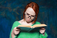 Girl red hair in green sweater and glasses reading book. Beautiful red-haired girl in a green sweater and glasses reading a book over magic dark blue background Stock Photography