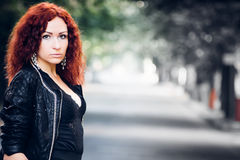 Girl with red hair on green trees alley. Portrait of a girl with red hair on city road whith green trees alley royalty free stock photo