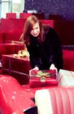 A girl with red hair is holding a box with a gift, which lies on a red car. The concept of festive mood and nice gifts royalty free stock photos
