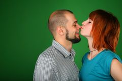Girl with red hair kisses guy on nose royalty free stock photography