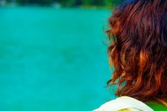 Girl with red hair at lake. Blur background. stock photography
