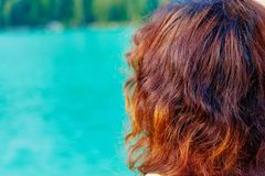Girl with red hair at lake. Blur background. stock photo