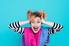 Girl with red hair laughing holding his head. Tangled hair. positive emotions. Studio shot. Blue background stock image