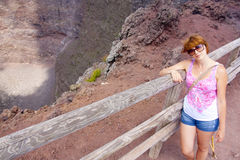 The girl with red hair is leaning against the fence at the crater of the volcano Vesuvius Royalty Free Stock Image