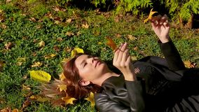 Girl with red hair lies on grass and holds fallen yellow autumn leaves in park stock video footage