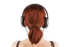 Girl with red hair listening to music. Stock Photos