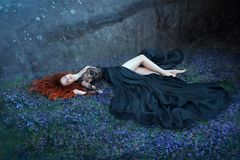 Girl with red hair lying on grass in dark forest, black queen lost in battle, charming lady in long black royal dress. With lace on open chest, sexy hot nymph stock images