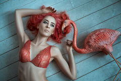 Girl with red hair lying naked on the floor. Royalty Free Stock Image