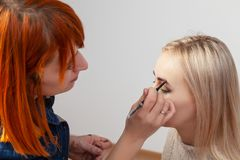 A girl with red hair - a make-up artist, draws out a blonde model`s eyebrow, with closed eyes and shadows in oriental style on th royalty free stock image