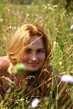 The girl with red hair on a meadow among a grass. Summer. Nature. Beautiful girl looks out of the grass. Goldilocks Royalty Free Stock Image