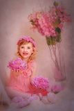 Girl with red hair in a pink dress and with flowers. Girl with long red hair sitting in a pink dress and with flowers Stock Images