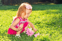 Girl with red hair playing with flowers in nature Stock Images