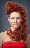 The girl with red hair in a red dress closeup Stock Photos