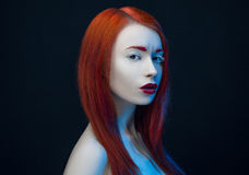 Girl with red hair red lips blue backlight Stock Images