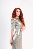 Girl with red hair and shiny silver dress. Beautiful girl with red hair and shiny silver dress standing Royalty Free Stock Photos