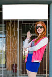 Girl with red hair shows a white sign Royalty Free Stock Photography