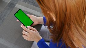 Girl with red hair sitting in cafe and using mobile phone with green screen. Close up. Girl with red hair sitting in cafe and using mobile phone with green stock video