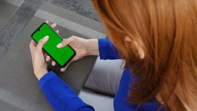 Girl with red hair sitting in cafe. Using mobile phone with green screen. Close up. Girl with red hair sitting in cafe. Using mobile phone with green screen stock video