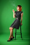 Girl with red hair smokes, sitting on stool Stock Photos