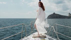 A girl with red hair stands on the bow of a yacht that rides along the sea along a rocky shore The wind is blowing a