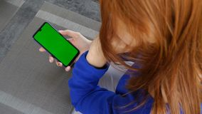 Girl with red hair using mobile phone with green screen. Close up. Girl with red hair using mobile phone with green screen stock video