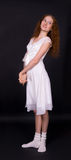 Girl with red hair wearing a white dress. Beautiful slender girl with red hair wearing a white dress Stock Image