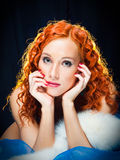 Girl with red hair wearing white fur on black Royalty Free Stock Photo