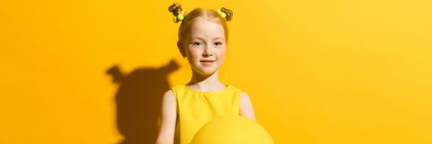 Girl with red hair on a yellow background. The girl is holding a yellow air balloon. Portrait of a beautiful girl in a yellow blouse and blue jeans stock image