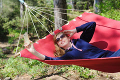 Girl in red hammock, woods Stock Images