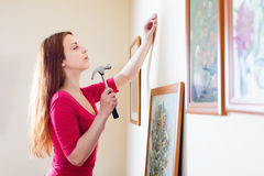 Girl in red hanging  pictures in frames Stock Image