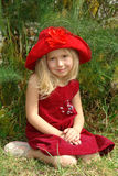 The girl in red hat. On the grass royalty free stock photography