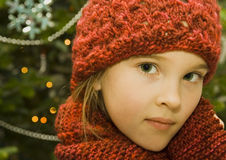 Girl in a Red Hat. Pretty little girl wearing a red knit hat and matching scarf standing in front of a decorated Christmas Tree Royalty Free Stock Images