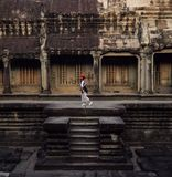 A Girl red hat adventure travellers walk on the wall at Angkor Thom Temple royalty free stock images