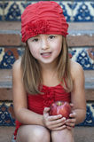 Girl in Red Hat, Holding an Apple Stock Photography