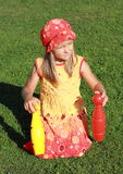 Girl in red hat kneeing with two bowls. Little girl in red and yellow dress kneeing on the grass and holding two bowls stock image