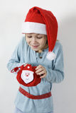 Girl in the red hat of Santa Claus gets gifts Royalty Free Stock Photos