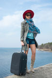 Girl in a red hat and with a suitcase in front of the sea Stock Photography
