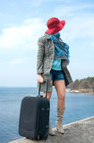 Girl in a red hat with a suitcase in front of the sea Stock Photography