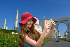 Girl in a red hat is taking a selfie in front of the mosque. Stock Photos